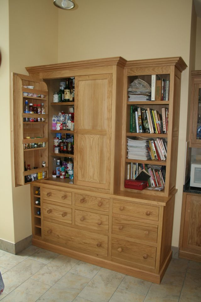 Oak larder unit fitted with, wine rack, shelving to back of doors, open bookcase and graded drawers