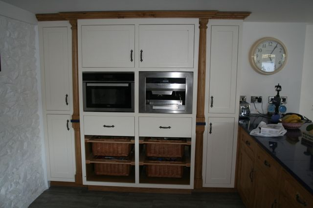Large larder unit with turned pillars, wicker baskets, microwave and integrated coffee machine