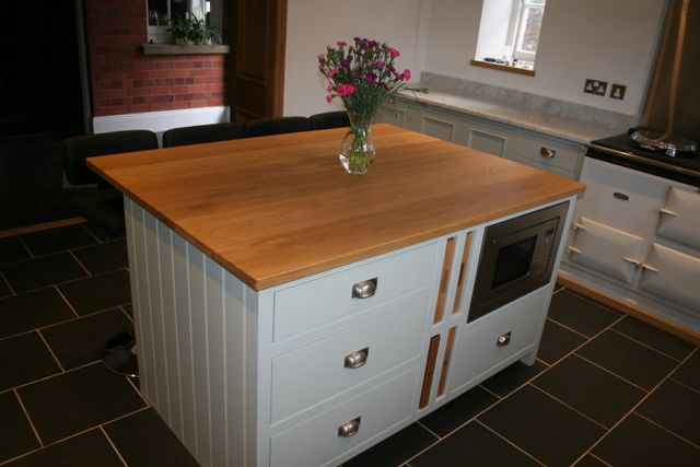 Island unit with solid oak worktop fitted with graded drawer unit, oak trays, oak chopping boards and built in microwave