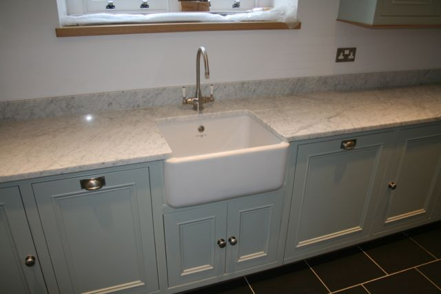 Sink area fitted with belfast sink, integrated dishwasher, wooden windowsill and stainless steel drawer pull, cup handle