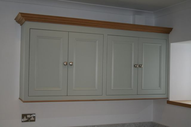 Painted wall units with contrasting bespoke hand made oak cornice and stainless steel knobs